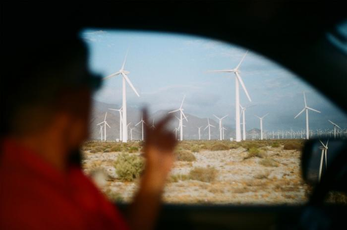 Man driving by a farm of wind turbines.