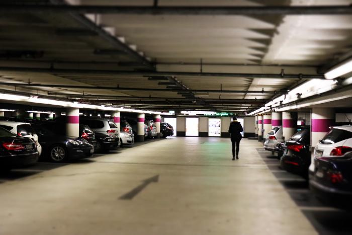 Man standing between cars in a residential parking garage